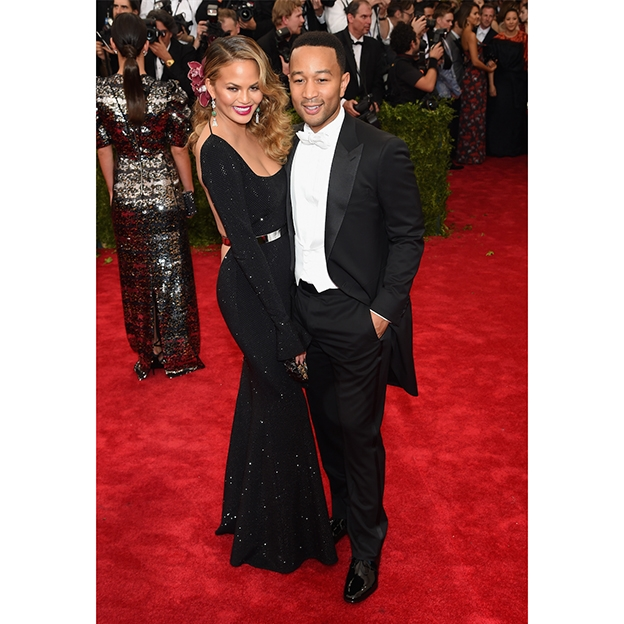 Chrissy Teigen smiling next to John Legend on the red carpet