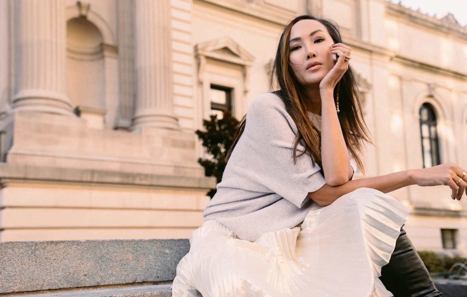 Chriselle Lim dressed in Saint John sitting down on some steps outside