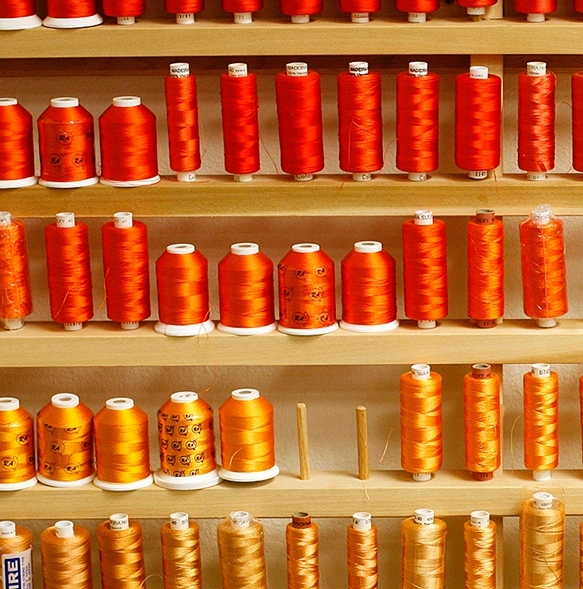 An array of red, orange, and yellow garment threads
