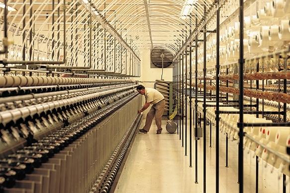 Worker handling knitting machine in design factory