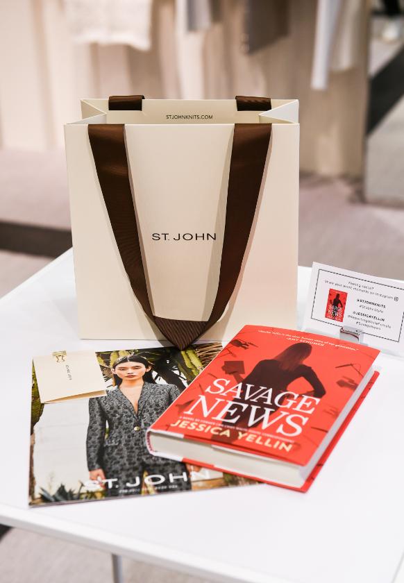 Savage News book next to Saint John shopping back and Pre-Fall 2019 catalog