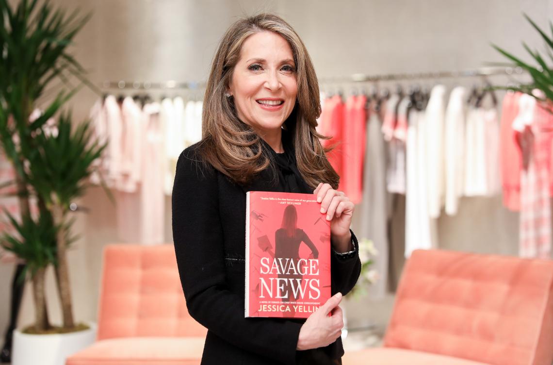 Jessica Yellin dressed in Saint John holding her new book Savage News