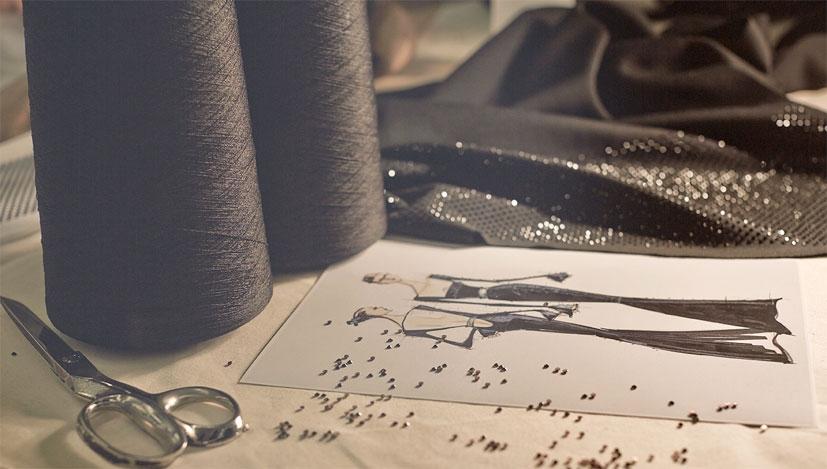 A fashion design sketch next to a roll of black thread